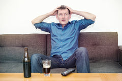 Man watching tv with tension Royalty Free Stock Photo