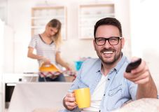 Man watching tv and woman doing housework. Young handsome man sitting on sofa and holding tv remote control while wife ironing and doing chores in background Royalty Free Stock Photography