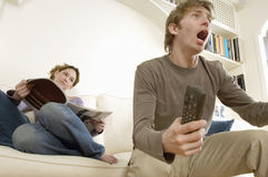 Man Watching TV With Woman Reading Magazine. Young men watching television and cheering with women reading magazine on sofa Stock Photography