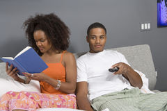 Man Watching TV While Woman Reading Novel Stock Photo