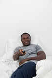 Man watching tv. Young man watching tv in his bedroom Stock Photo