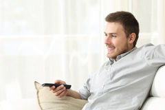 Man watching tv and zapping. Happy man watching tv and zapping sitting on a couch at home Stock Photo