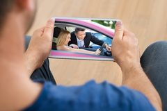 Man watching video on cellphone Stock Photo