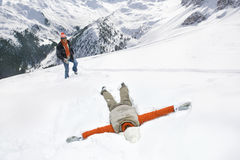 Man watching woman making snow angel on mountain Royalty Free Stock Photo