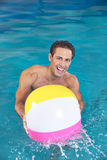 Man with water ball playing in pool Royalty Free Stock Image