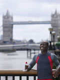 Man With Water Bottle Against Tower Bridge In England Royalty Free Stock Images