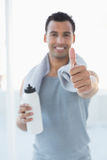 Man with water bottle and towel gesturing thumbs up in fitness studio Royalty Free Stock Photography
