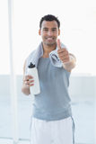 Man with water bottle and towel gesturing thumbs up in fitness studio Stock Image