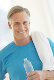 Man With Water Bottle And Towel At Gym. Portrait of happy mature man with water bottle and towel at gym stock photography