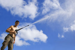 Man with water hose Royalty Free Stock Photos