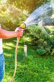 Man with water hose in the garden. Man with water hose watering the grass in the garden royalty free stock photos