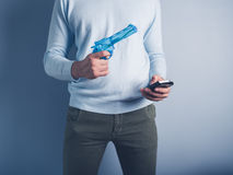 Man with water pistol and smart phone Stock Image