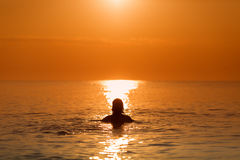 Man in Water on a sea in a sunrise Stock Image