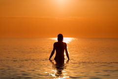 Man in Water on a sea in a sunrise Stock Photo