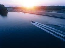 Man water skiing on lake behind boat Stock Photos
