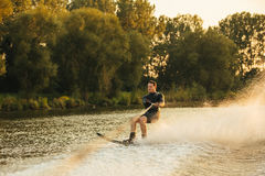 Man water skiing on lake behind a boat Stock Image