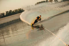 Man water skiing on lake. Wakeboarder surfing across the lake behind motorboat. Man water skiing on lake with water splashes Royalty Free Stock Photos