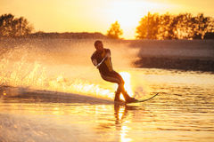 Man water skiing at sunset. Outdoor shot of man water skiing at sunset . Man wakeboarding on a lake Royalty Free Stock Photo