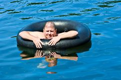 Man in Water with Tube. A man in water floating on an inner tube Stock Image