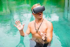Man in water with virtual reality glasses stock images