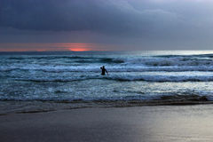 A man in water watching sunrise. Stock Images