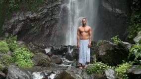 man at waterfall stock video