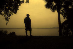 Man by the Waterfront Silhouette Stock Photos