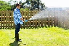 Man watering backyard lawn. Young man watering backyard lawn using hosepipe Stock Photo
