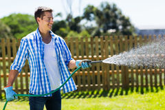 Man watering garden. Cheerful man watering home garden Stock Photo