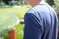 Man watering the garden with a sprinkler hose on a sunny day. Man watering the garden with a sprinkler hosepipe on a sunny day stock images