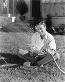 Man watering the grass and reading Royalty Free Stock Images