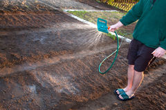 Man watering the ground Stock Photography