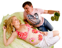 Man watering pregnant belly Royalty Free Stock Images