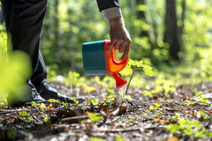 Man watering with a toy watering can Royalty Free Stock Images