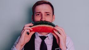 A man and a watermelon / Boy in classic suit with a watermelon. Boy in classic suit with a watermelon / A man and a watermelon n Stock Photo