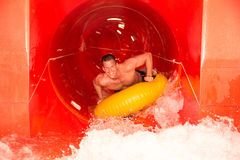 Man in waterslide at public swimming pool Stock Photography