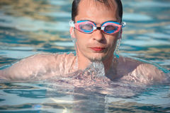 Man in watersport goggles swimming in pool Stock Image