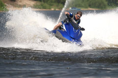 Man on Wave Runner. Turns fast with much splashes Royalty Free Stock Photography