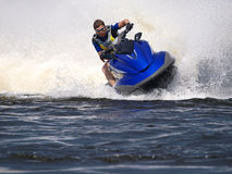 Man on Wave Runner on the water. Man on Wave Runner rides fast with much splashes Stock Image