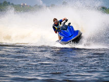 Man on Wave Runner on the water. Man on Wave Runner rides fast with much splashes Stock Photos