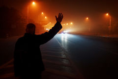 Man waves for taxi on misty night royalty free stock images