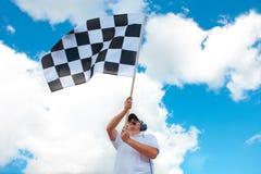 Man waving a checkered flag on a raceway. Man with headset holding and waving a checkered flag on a raceway Stock Image