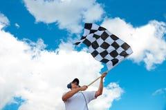 Man waving a checkered flag on a raceway. Man with headset holding and waving a checkered flag on a raceway Stock Photo