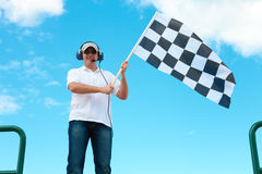 Man waving a checkered flag on a raceway Stock Photo
