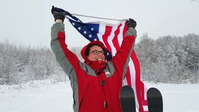 Man with US flag on a ski slope. Man waving a flag of the united states in winter on a ski slope stock video