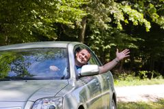 Man waving hand from car. Young woman happy about her new car Royalty Free Stock Image