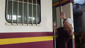 Man waving hand at passenger train door. stock video footage