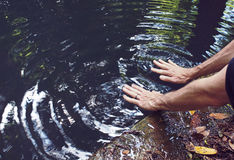 Man Waving Hands on Surface of Pond Royalty Free Stock Image
