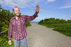 Man waving his hand and smiling Stock Images