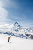 A man waving his hand standing on the snow in the background of Matterhorn. Zermatt, Switzerland royalty free stock image
